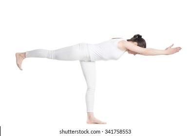 Sporty beautiful young woman in white sportswear standing in Warrior III posture (Virabhadrasana 3), Balancing Stick Pose (Tuladandasana), studio shot, isolated, full length side view
