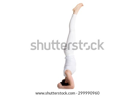 Sporty beautiful young woman in white sportswear doing Supported headstand exercise, salamba sirsasana 1, studio full length isolated shot, side view