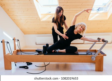 Sporty blond curly senior woman doing pilates exercises in gym with help from female physical therapist or instructor.