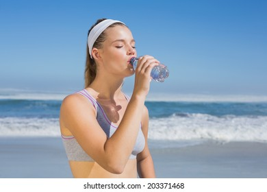 Sporty blonde drinking water on the beach on a sunny day