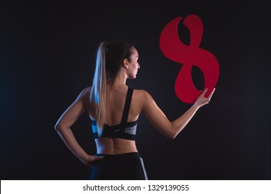 sporty blonde holds the figure eight in the hands on a black background