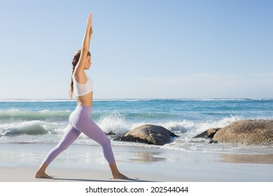 Sporty blonde stretching on the beach on a sunny day