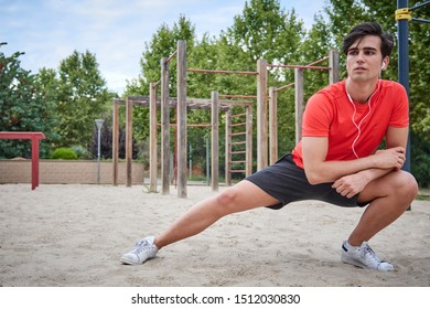 sporty boy doing leg stretches before or after practicing calisthenics, he wears a red shirt and the bottom is green and blue, he moves very to the right