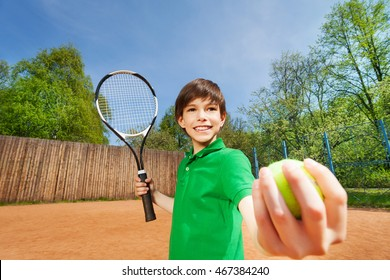 Sporty boy starting tennis set on the clay court
