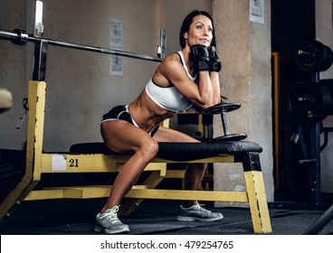 Sporty brunette female posing on barbell stand in a gym club.