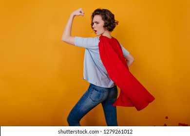Sporty brunette girl in carnival costume fooling around in studio. Portrait of funny young lady pretending superhero.