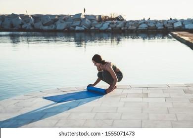 Sporty brunette woman in green sportswear unrolling blue mat before starting training yoga outside on embankment near water in morning