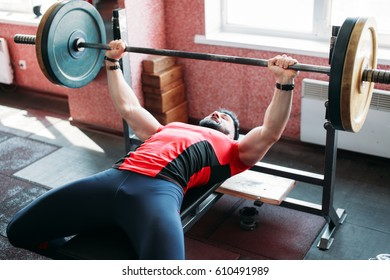 Sporty brutal strong guy doing exercises with a barbell in the gym. Brutal sports man. Bodybuilder in training in the gym. Health and fitness