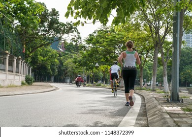 Sporty Caucasian woman running on the road in the Asian city park with green tree row in early morning