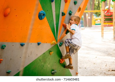 Sporty children climbing artificial boulder on practical wall in gym
