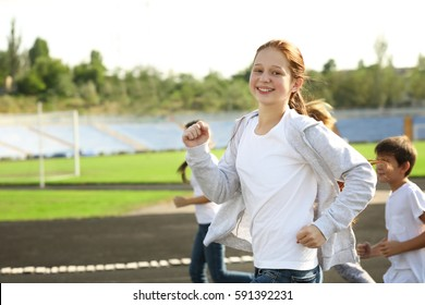 Sporty children running on track at stadium