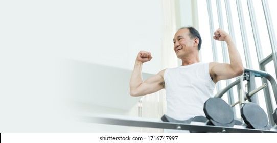 Sporty confident Elderly male in white sportswear smiling while workout. Strong powerful Asian senior man showing biceps and huge arms muscle while exercise at the gym. Lifestyle, Healthy. Banner