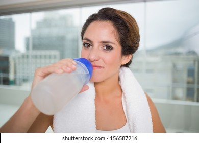 Sporty content brunette holding water bottle in bright room