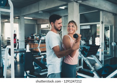 Sporty couple exercising dumbbell weights lifting in fitness gym., Portrait of attractive young couple are practicing workout in training class., Beautiful woman with trainer exercise weights lifting.