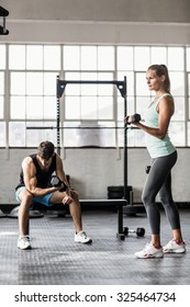 Sporty couple exercising with dumbbells in crossfit gym