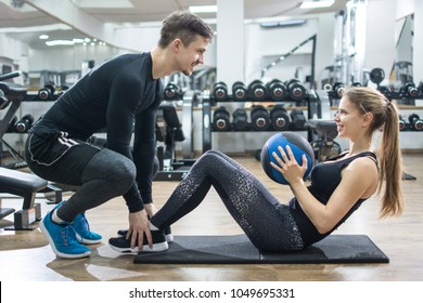 Sporty couple exercising together in gym. Handsome man assisting beautiful girl while doing sits ups with medicine ball in fitness centre.
