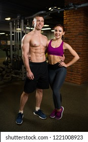 Sporty couple in the gym. Man with naked torso and beautiful girl in the sport clothes.