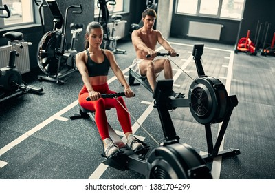 Sporty couple in gym. Young attractive woman and handsome muscular man doing exercises on rowing machine