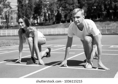 Sporty couple start competition running at arena track on a sunny summer day outdoor