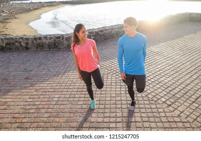 Sporty couple stretching legs next to the beach - Young lovers traning together on summer day outdoor - Sport, relationship, healthy lifestyle concept