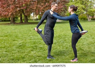 Sporty couple stretching for warm up at the park