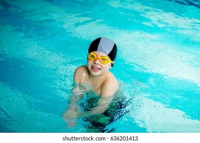 Sporty cute little boy splashing and playing in swim pool.