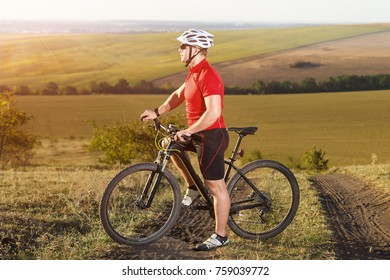 Sporty cyclist with red backpack standing on the top of a hill against beautiful landscape. Sportsmanin the sportwear, orange jacket, sunglasses and helmet. Summer season in the countryside.