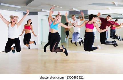Sporty different ages adults jumping at dance class