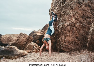 Sporty disabled woman working out outdoors and doing handstand exercise on the beach