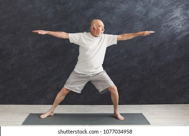 Sporty elderly guy practicing yoga indoors. Senior man doing stretching exercise, black background. Active lifestyle and healthcare in any age, copy space