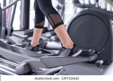 Sporty exercise elliptical cardio running workout at fitness gym of woman taking weight loss with machine aerobic for slim and firm healthy lifestyle.