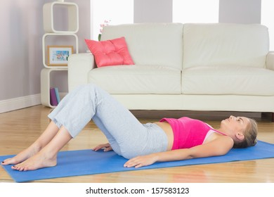 Sporty exhausted blonde lying on exercise mat in bright living room