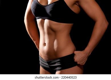 Sporty female body on black background. Shoot in studio.