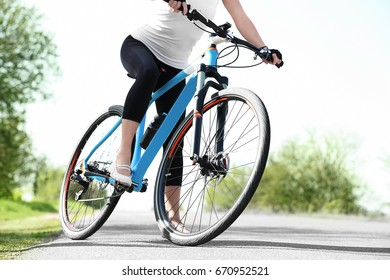 Sporty female cyclist with bicycle outdoors on sunny day