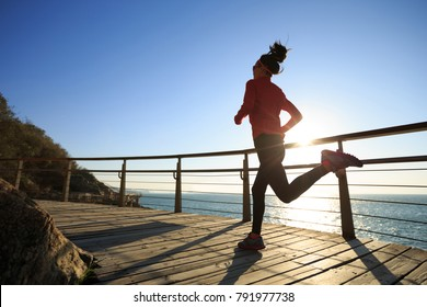 sporty female jogger morning exercise on seaside boardwalk during sunrise