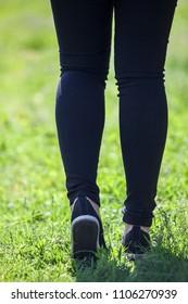 Sporty female legs jogging on summer meadow in light sneakers, rear view