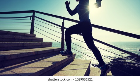 sporty female runner running upstairs on coast trail