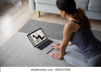 Sporty female sit on floor at home watch video training on computer, take online class or course. Woman practice yoga mediate on video call or webcam digital virtual lesson with private instructor.