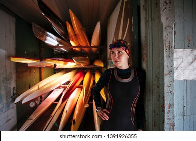 Sporty female young athlete is smiling and standing surrounded by Collection of vibrant colorful plastic recreational canoe and kayaks stored storage rack, side view!