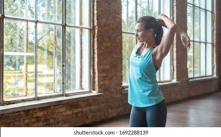 Sporty fit active young woman in sportswear warming up stretching arms stand alone in modern studio gym, female healthy girl bodybuilder do sport workout exercise fitness training concept, copy space