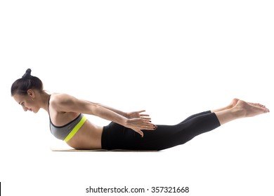 Sporty fit beautiful young brunette woman in sportswear bra and black pants working out, doing Salabhasana, Locust, Grasshopper Pose, Double Leg Kicks, studio full length, isolated, white background