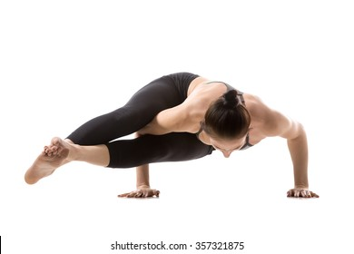 Sporty fit beautiful young brunette woman in sportswear bra and black pants working out, doing Astavakrasana, asymmetrical arm balance Eight-Angle Pose, studio full length, isolated, white background