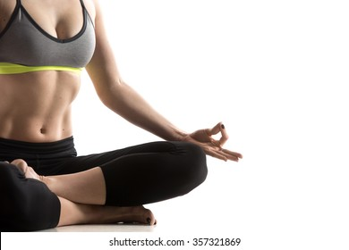 Sporty fit beautiful young woman in sportswear bra and black pants working out, sitting in Fire Log pose, Square Posture for hips and groins, studio close-up, isolated, white background