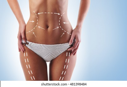 Sporty and fit girls body with arrows. Fat lose, liposuction and cellulite removal concept.
