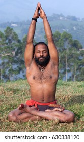 Sporty fit Indian man in lotus yoga pose on green grass does breathing exercises in Kerala, South India