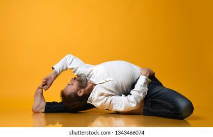 Sporty fit old man in jeans practices Ashtanga Vinyasa yoga back bending asana Paschimottanasana - seated forward bend