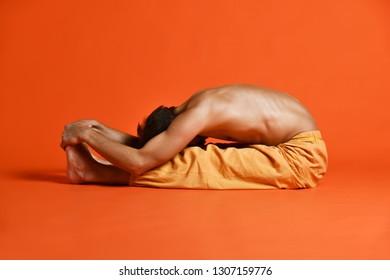 Sporty fit old man practices Ashtanga Vinyasa yoga back bending asana Paschimottanasana - seated forward bend