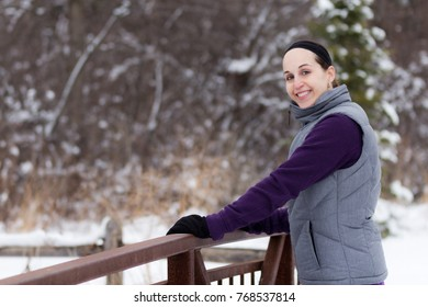 Sporty fit woman outdoor in winter forest trail.  Fitness and wellness lifestyle concept