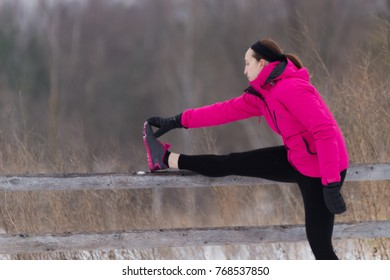 Sporty fit woman stretches her hamstrings before running on trail on cold winter day. Wellness workout and healthy lifestyle concept.