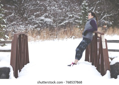 Sporty fit woman in winter running clothing relaxes along nature trail. Fit healthy lifestyle concept with beautiful young fitness model.